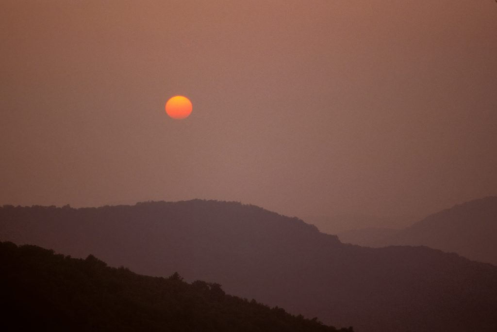 Photograph of the sun drifting through atmospheric layers causing a gradient of color from yellow to red in the Tennessee mountains one summer evening
