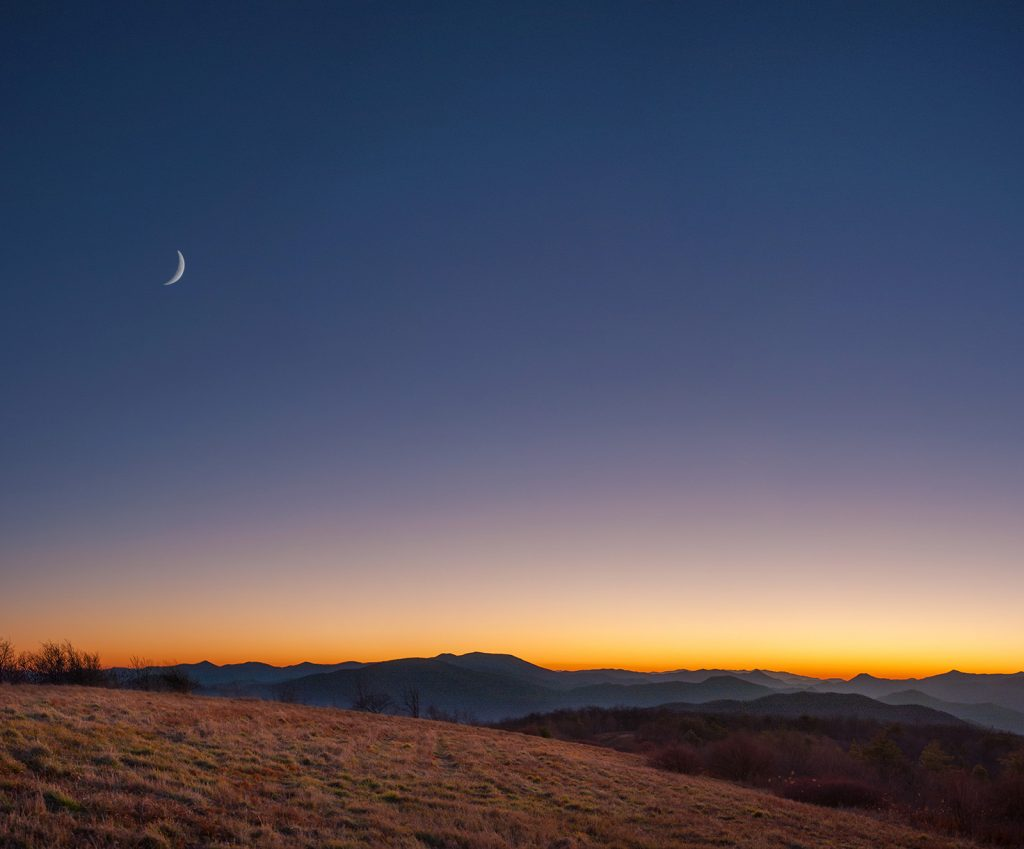 Photograph of a mountain scene, after sunset, and a crescent moon