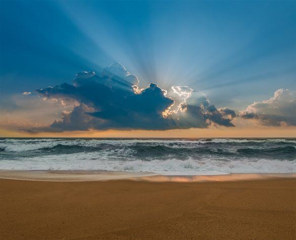 Rays of light from the sun appear in the sky from a cloud over the Pacific Ocean
